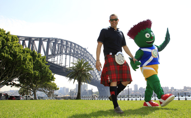 Commonwealth Games Glasgow 2014 mascot Clyde and Scottish swimming champion Gregor Tait walk in front of the Sydney Harbour Bridge, Tuesday, Oct. 29, 2013. (AAP Image/Daniel Munoz) NO ARCHIVING